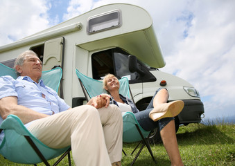 Senior couple relaxing in camping folding chairs