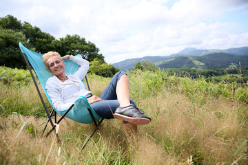 Senior woman relaxing in chair in countryside