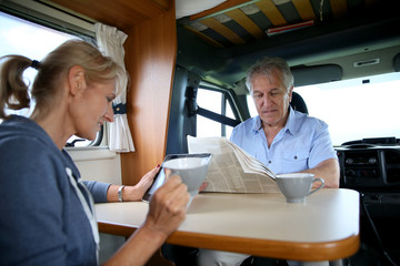 Senior couple relaxing inside camper