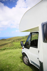 View of camper parked on hill by the sea