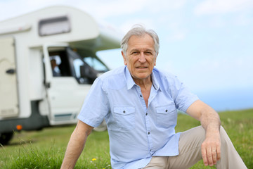 Senior man sitting on grass, camper in background