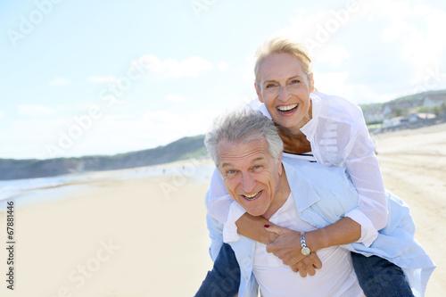 Senior man giving piggyback ride to wife - 67881446