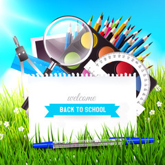 Back to school background with school supplies in the grass