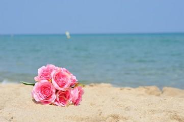 砂浜とピンクの花束