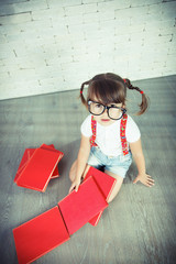 Little nerd girl with glasses and books.