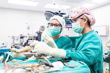 two scrub nurse preparing tools