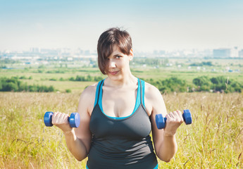Beautiful plus size woman exercising with dumbbells
