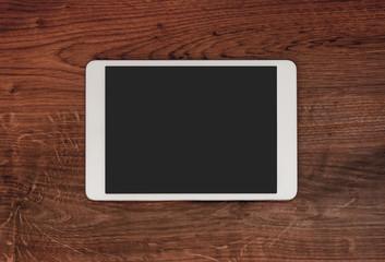 Blank modern digital tablet on a wooden desk. Top view. High qua