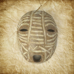 A tribal mask from Africa on old paper background