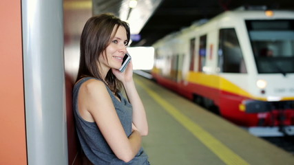 Young woman talking on cellphone at train station