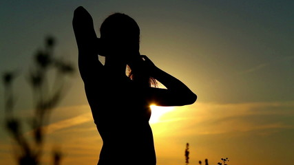 Girl posing at sunset. Woman at sunset in the field.