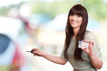 Mädchen hält Autoschlüssel und neuen Führerschein