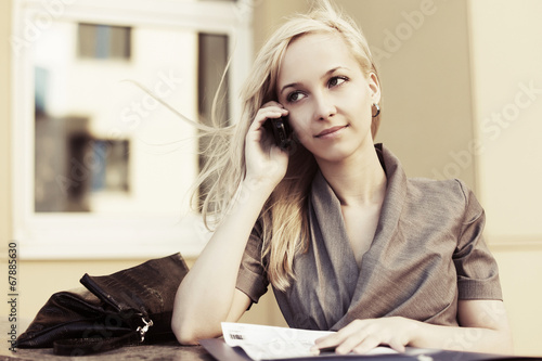 Blond fashion business woman calling on the cell phone