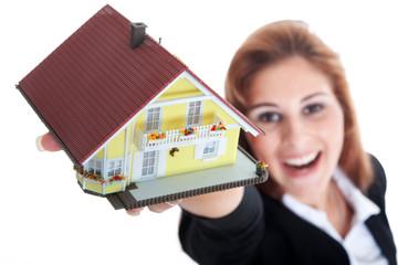 Junge glückliche Frau mit Miniatur Haus lacht