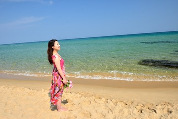 一人で楽園を旅行しているピンクの服の女性
