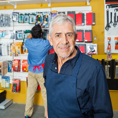 Confident Senior Worker Smiling In Hardware Store