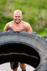 Male Athlete Doing Tire-Flip Exercise