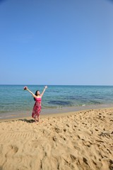 ピンクのワンピースを着て海で手を挙げているアジア人女性