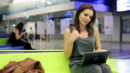 Beautiful woman working on laptop at train station