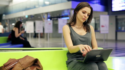 Woman with laptop walk away in hurry for train at train station