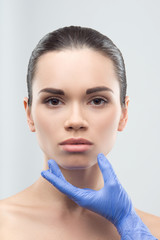 Beautician in rubber gloves touching face of young beautiful wom