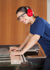 Happy Female Carpenter Using Tablesaw