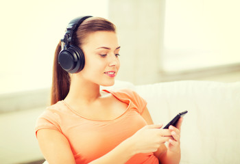 woman with headphones and smartphone at home