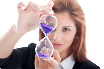 Geschäftsfrau blickt kritisch auf Sand Uhr