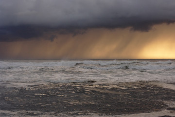 Sea storm at sunset