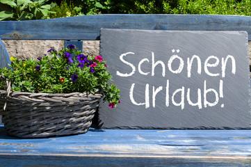 Blaue Holzbank mit Kreidetafel und Schönen Urlaub