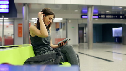 Woman listen to music on smartphone at train station