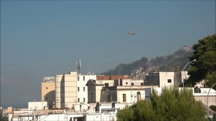 plane flies over buildings near the fire