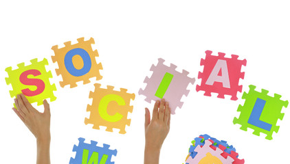 "Hands forming word ""Social"" with jigsaw puzzle pieces isolated"
