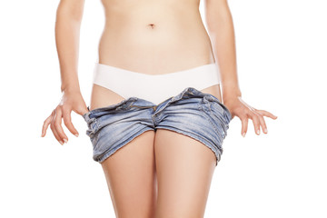 woman undresses her short jeans pants