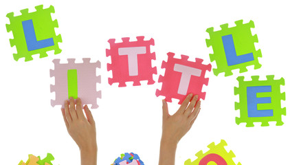 "Hands forming word ""Little"" with jigsaw puzzle pieces"
