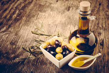 Fresh olives olive oil rustic wooden background
