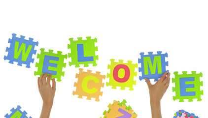 "Hands forming word ""Welcome"" with jigsaw puzzle pieces isolated"