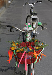 bike with  basket decorated with blooms parked on street