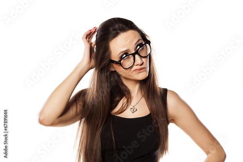 Leinwanddruck Bild unsure young woman scratching her head