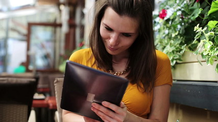 Elegant woman with tablet computer sitting in cafe