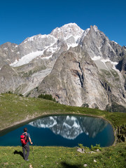 A hiker takes a rest looking at Mont Blanc, the highest peak in