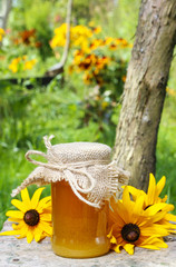Jar of honey and beautiful sunflowers in the garden