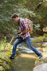 young photographer crossing stream at mountain valley