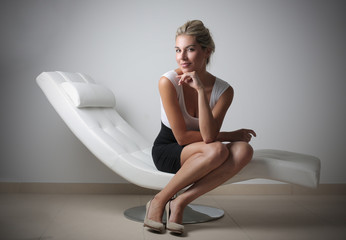 beautiful business woman sitting on a chaise longue
