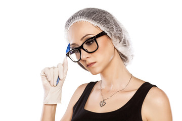 thinking young woman with pen, protective cap and gloves