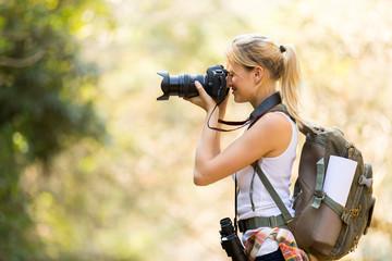 female photographer taking photos in mountain valley