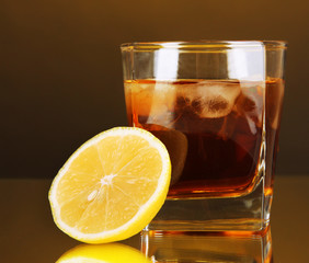 Glass of whiskey with ice and lemon on yellow background