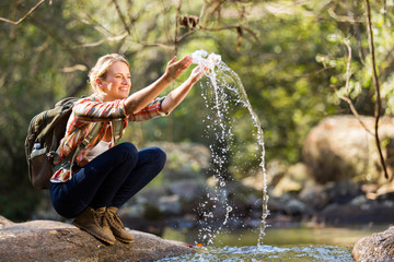 young hiker playing with stream water