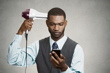 Executive holding smart phone, drying his hair out