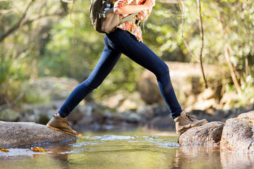 young hiker crossing stream in mountain